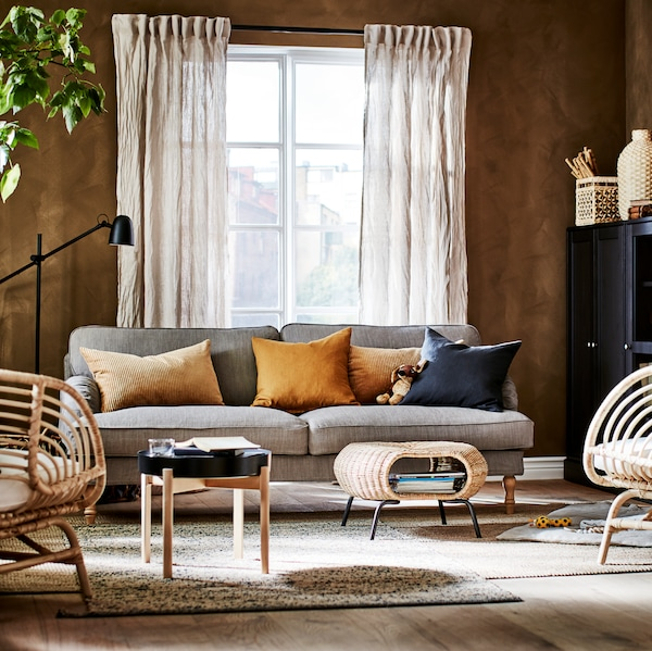 Une pièce avec un canapé gris et des coussins de différentes couleurs, une table basse, des chaises, devant une fenêtre habillée de rideaux.