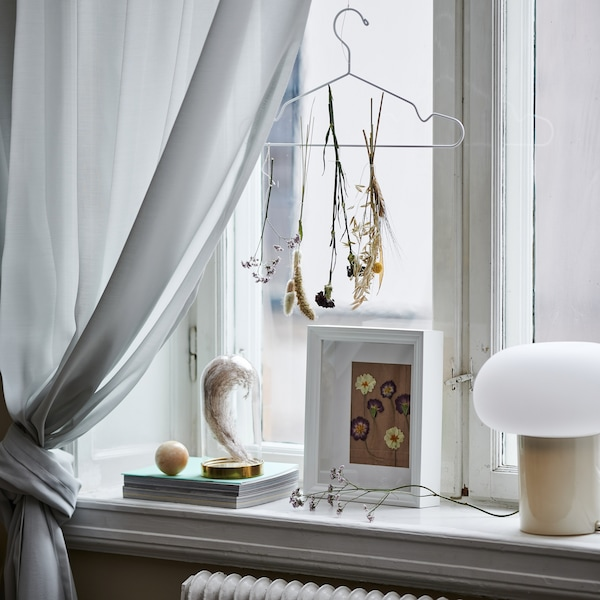 A window sill decorated with photoframe and other decorative objects.