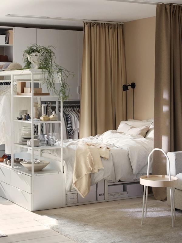 Hvidt PLATSA sengestel med fire skuffer for enden og hylder samt en garderobestang, hvor der hænger tøj på.