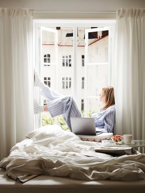 Kvinna i ljusblå pyamas sittande i fönster vis en säng med vita påslakan.