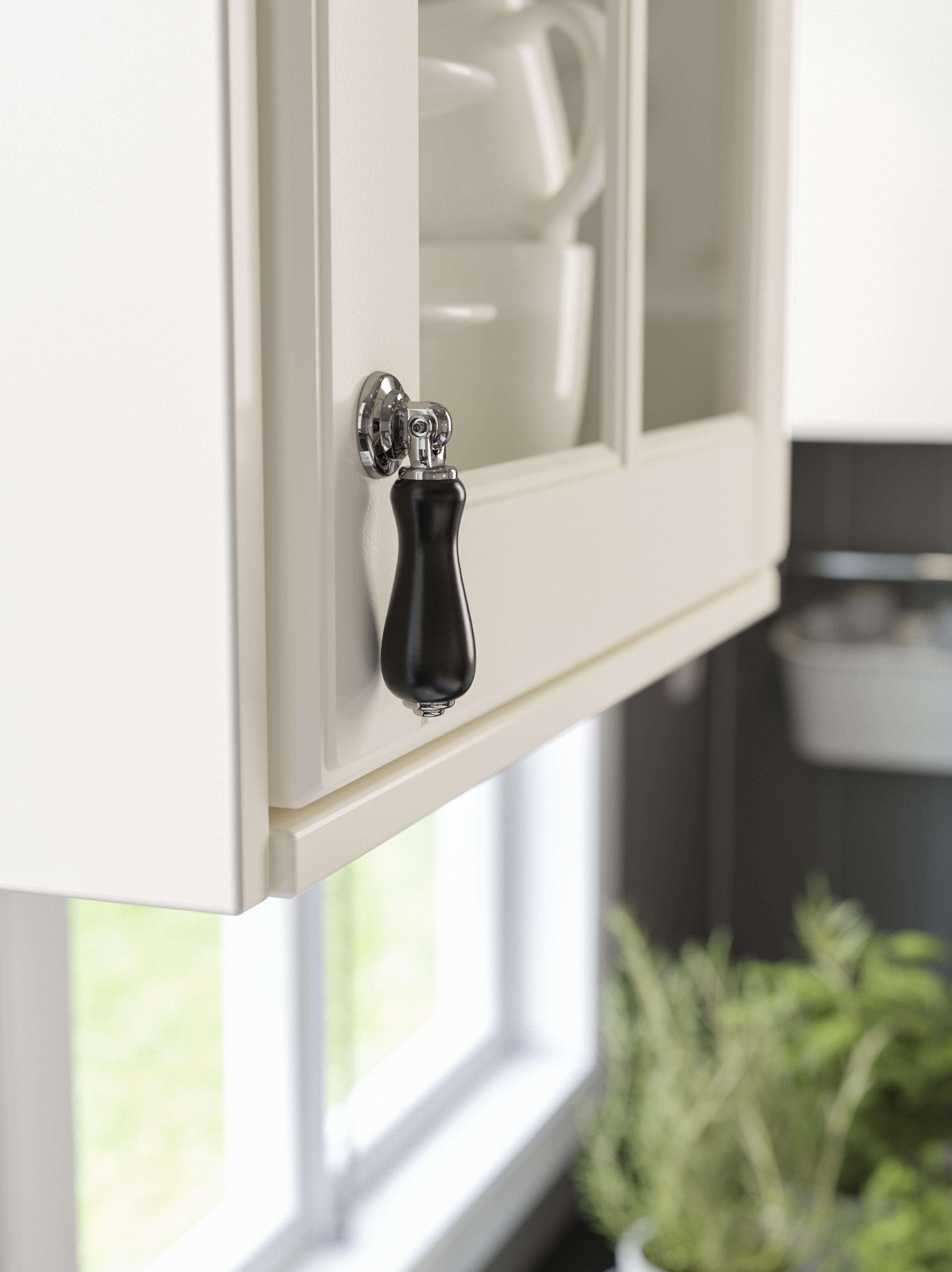 A close-up of an IKEA SKÄRHAMN smooth black drop handle with chrome plated edges on a white kitchen door.