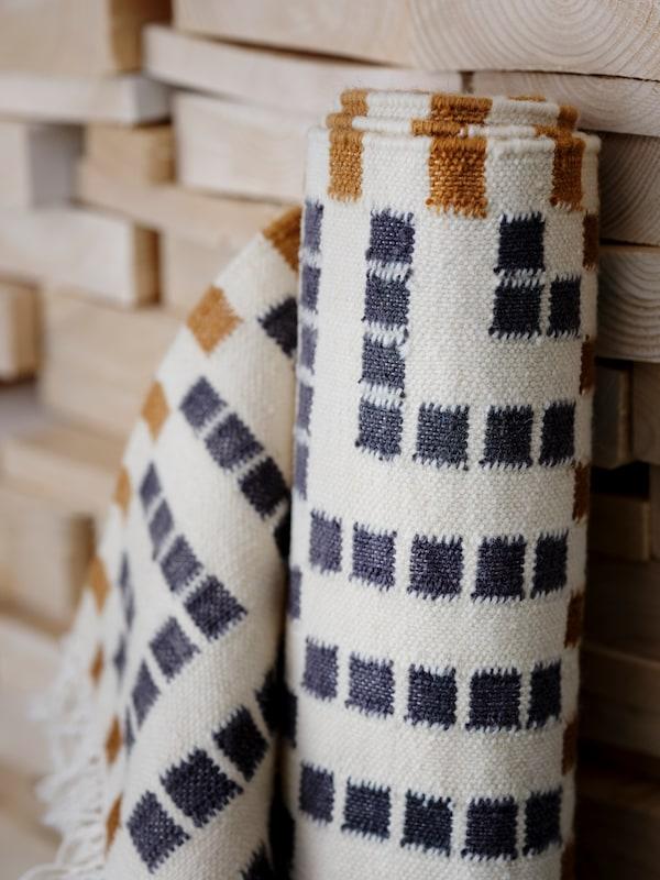 Close-up af et håndlavet, multifarvet VAMDRUP fladvævet tæppe, som er rullet sammen og læner sig op ad stablede planker.