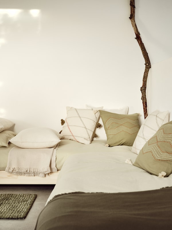 In the corner of a room, a cozy day bed is scattered with HERVOR and HALLVI cushion covers in off-white and green.