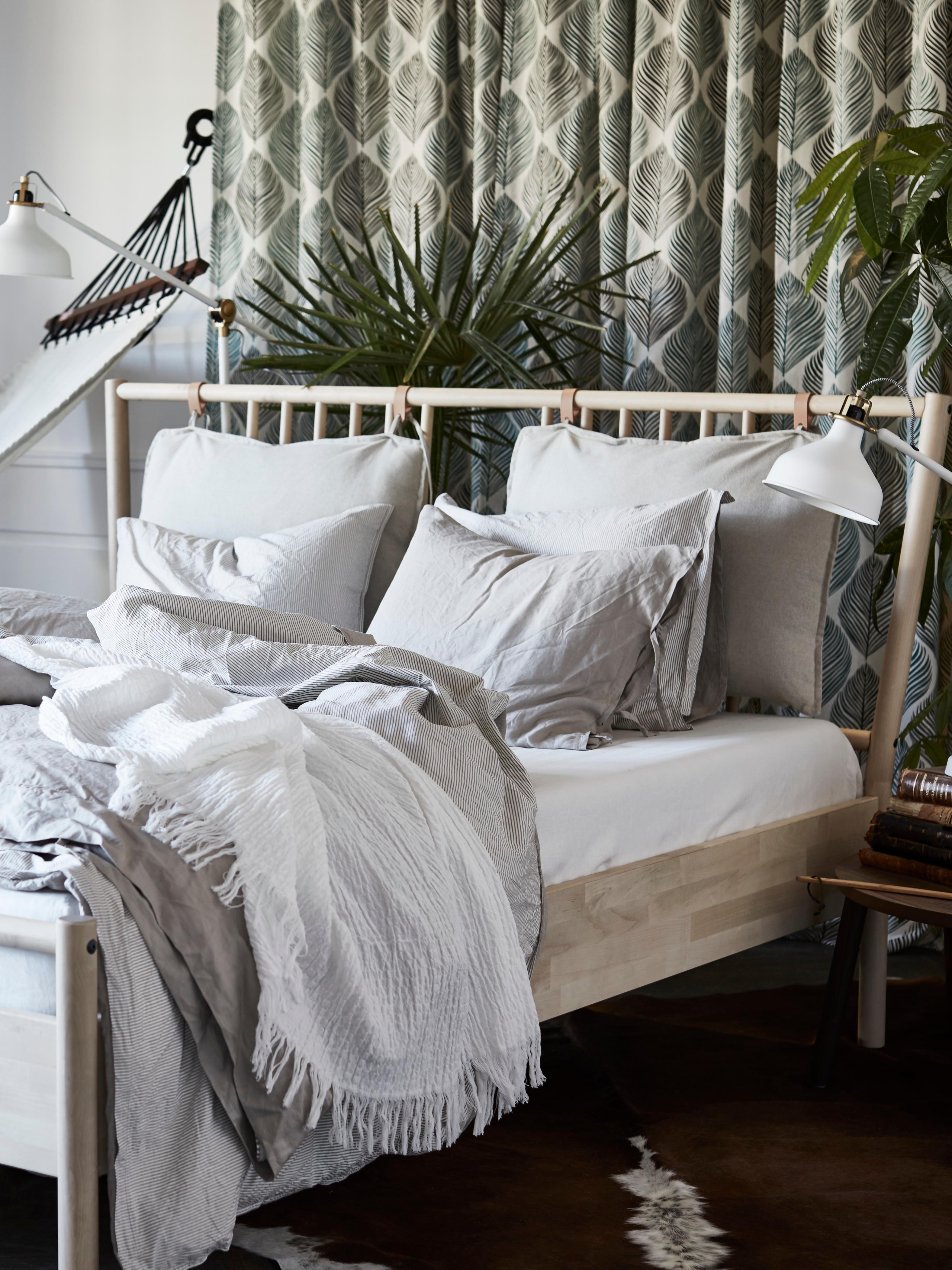 Estrutura de cama BJÖRKSNÄS em bétula, com capa para edredão em bege, em cima de tapete em pele de vaca, junto a cama de rede num quarto com plantas.