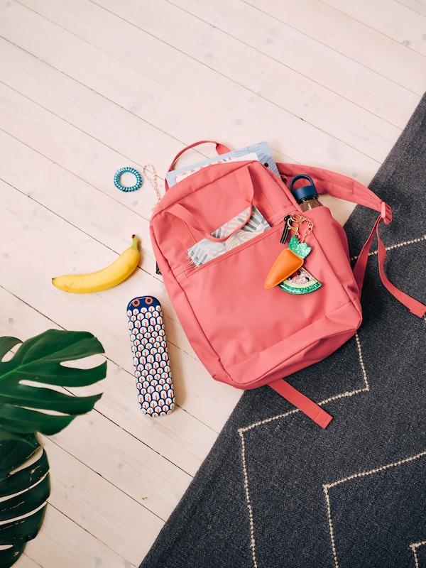 Un rucsac STARTTID roz-roșu pe podea, cu un caiet și o sticlă de apă în buzunare, și un penar alături.