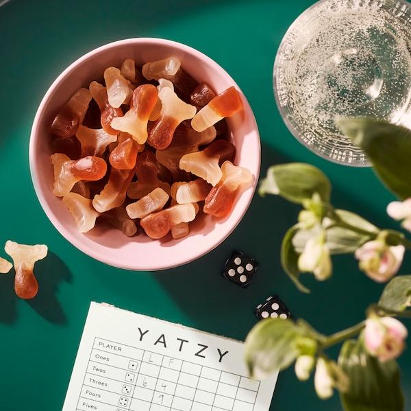 Na zelenom stole je miska so želé cukríkmi LÖRDAGSGODIS, vedľa sú kvety a kocky na hranie.