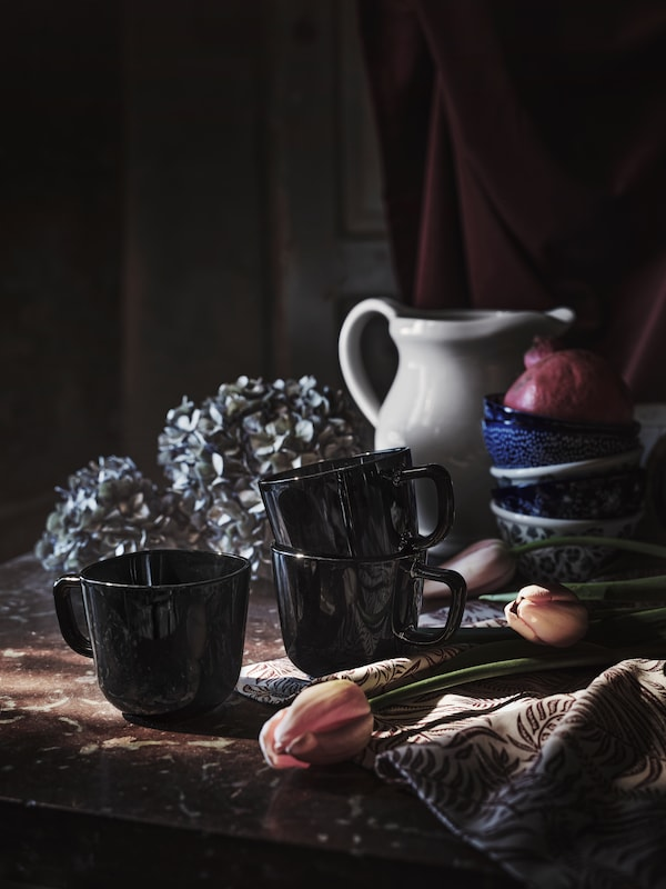 Three black BACKIG mugs on a table beside a pile of blue bowls and a grey jug near some tulips and other flowers.