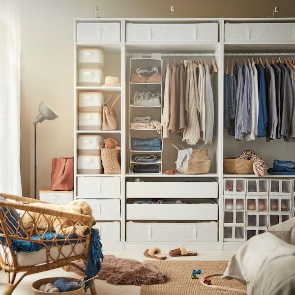 Eine offene PAX Kleiderschrankkombination mit Kleidung und Inneneinrichtungen wie Schubladen, Kleiderstangen, Körben und Taschen.