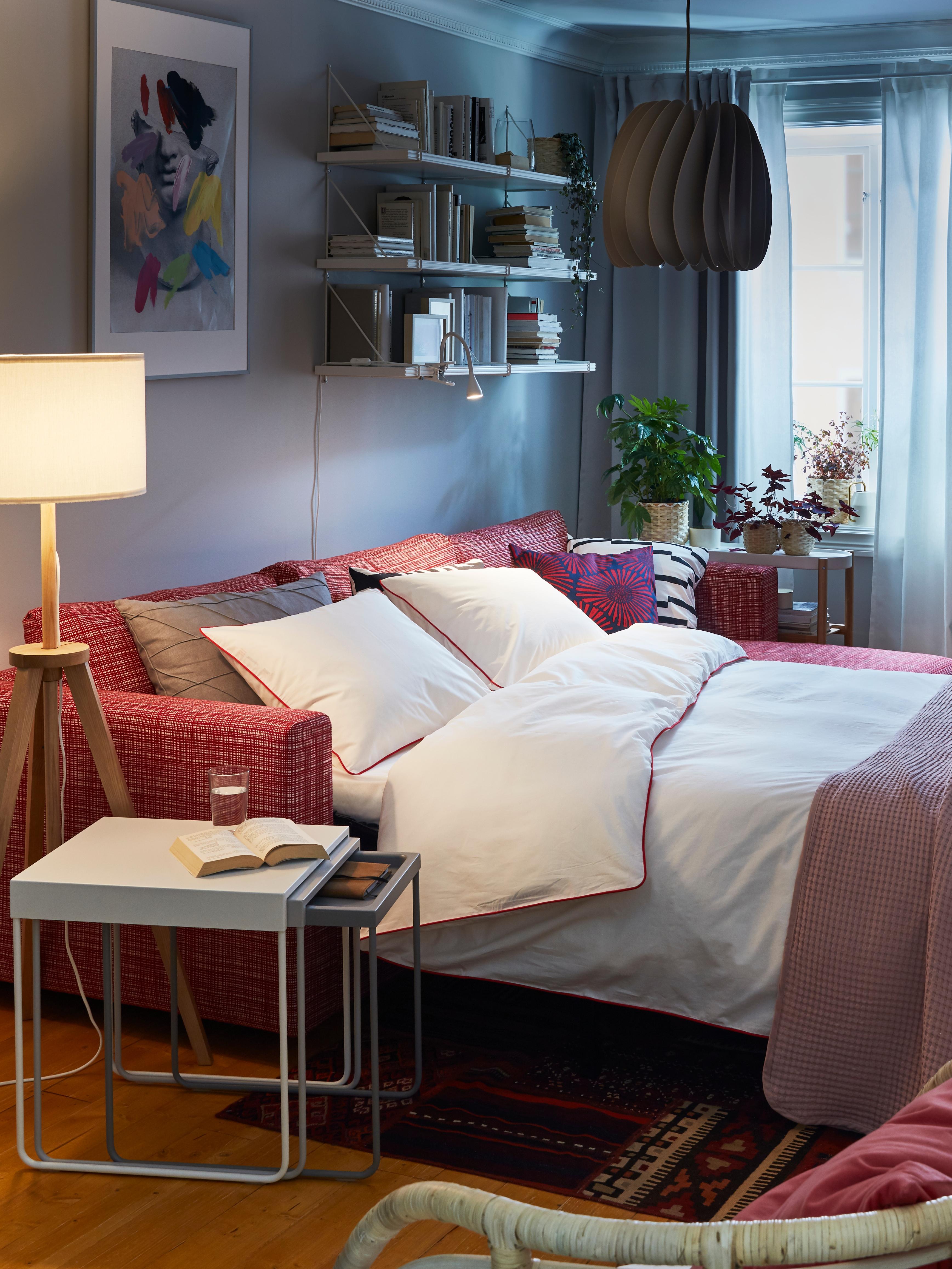 Crveno-beli VIMLE sofa ležaj s tri sedišta u funkciji kreveta s belom posteljinom pored seta stočića i uključene podne lampe.
