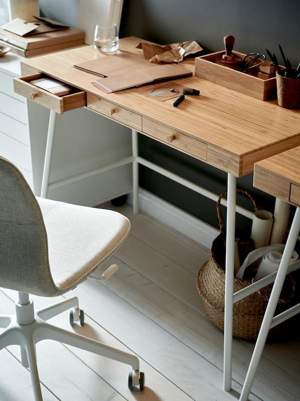 Egy LILLÅSEN íróasztalt látunk bambusz asztallappal, beépített fiókokkal és fehér lábakkal. Rajta íróasztali rendszerezők, mellette pedig bézs/fehér LÅNGFJÄLL irodai szék kapott helyet.