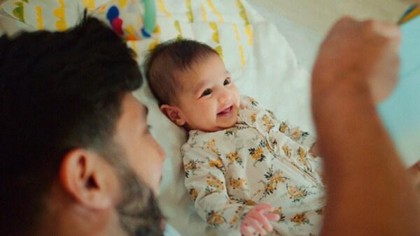 Uomo con la barba insieme a un bimbo piccolo sorridente sul letto.