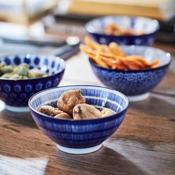 Des bols en céramique japonais à motif bleu sont remplis de fruits secs et de dattes.