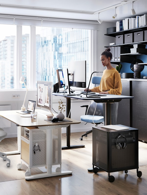 A woman stands at a work desk, with a screen and a chair, another lower desk with screen and diverse items, and storage.