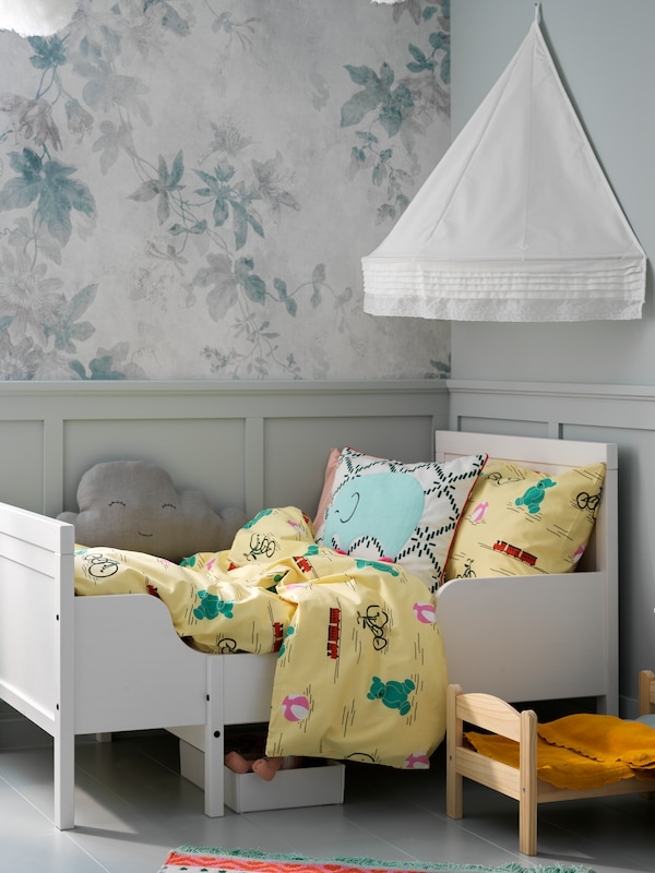 A white SUNDVIK bed, with KÄPPHÄST bed linen and a white LEN bed canopy above it, stands next to a DUKTIG doll's bed.