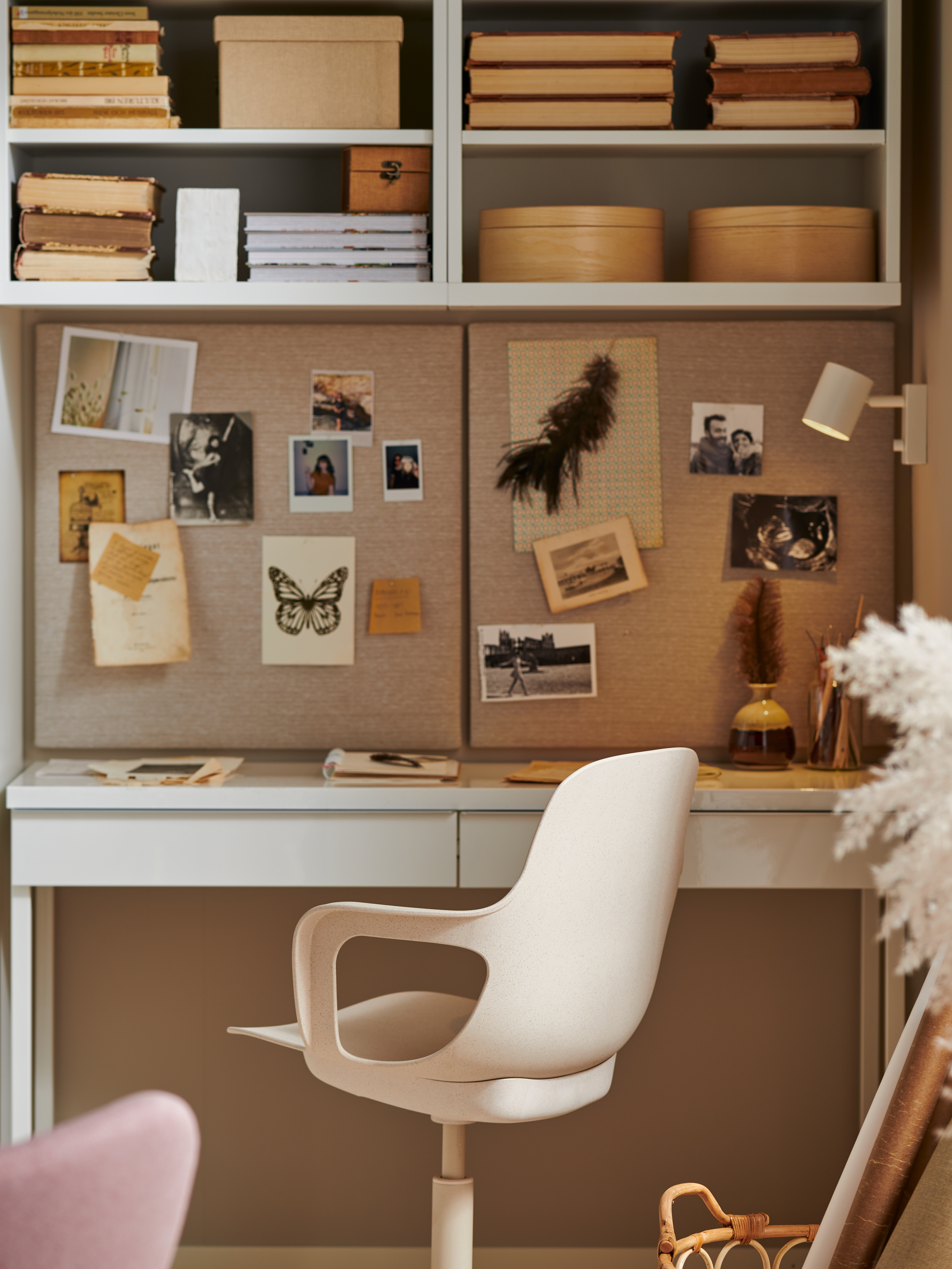 A workspace with a high-gloss white BESTÅ BURS desk, a swivel chair, two memo boards with pins, books, boxes and photos.