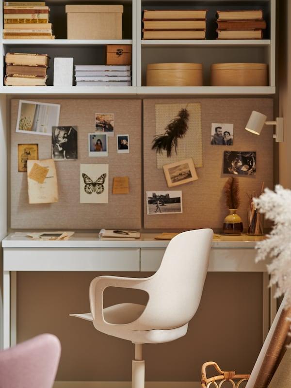 Un espace de travail avec un bureau BESTÅ BURS au fini blanc très brillant, une chaise pivotante, deux tableaux d'affichage avec des punaises ainsi que des livres, des boîtes et des photos.