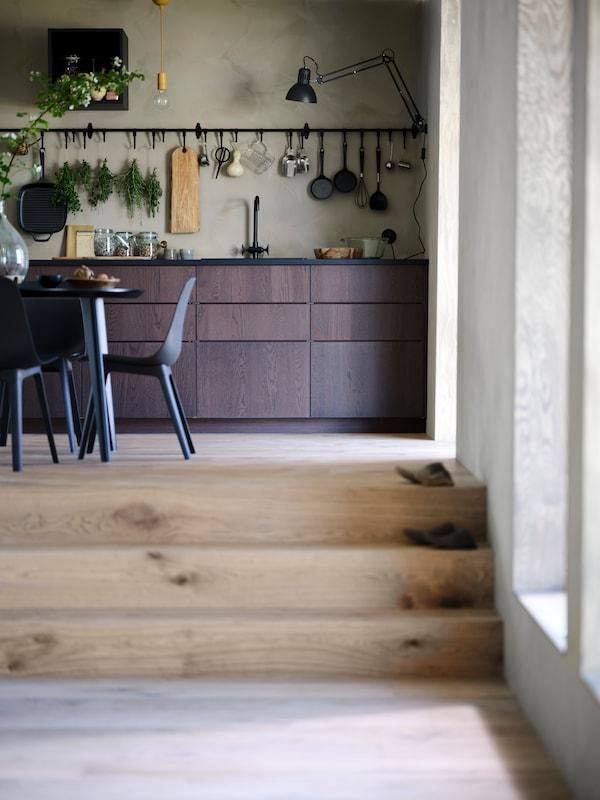 Unha cociña SINARP cunha mesa LISABO e cadeiras ODGER, unha guía HULTARP montada en parede, utensilios e herbas pendurando de ganchos.