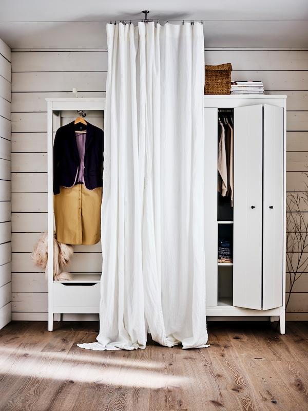 Ein weisser IDANÄS offener Kleiderschrank, daneben ein weiterer IDANÄS Kleiderschrank. Davor hängt eine DYTÅG Gardine.