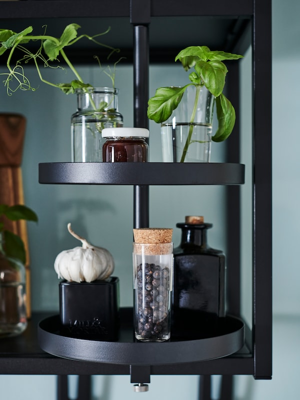 A black ENHET swivel shelf with two layers is attached to an open shelf, displaying plant cuttings and spices.