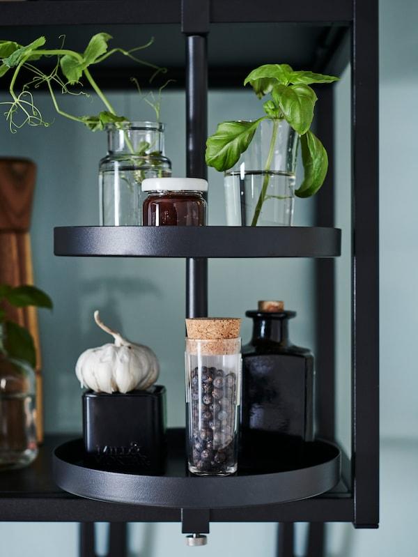 Une tablette pivotante ENHET noire à deux niveaux est fixée sur une étagère ouverte où sont placées des boutures de plantes et des épices.