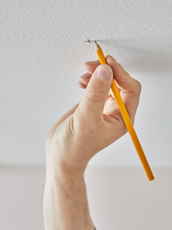 A person's hand marking a spot on the ceiling for a hole for mounting a VIDGA curtain track rail to the ceiling.