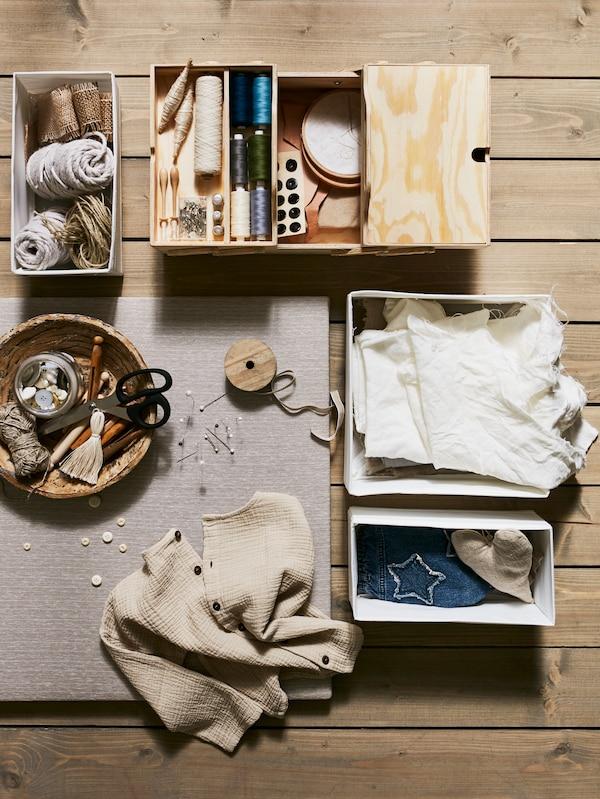 Blick aus der Vogelperspektive auf drei SKUBB Boxen, ein KLÄMMEMACKA Schreibutensilienfach aus Spanplatte und eine Schüssel mit Kleidung und Nähutensilien.