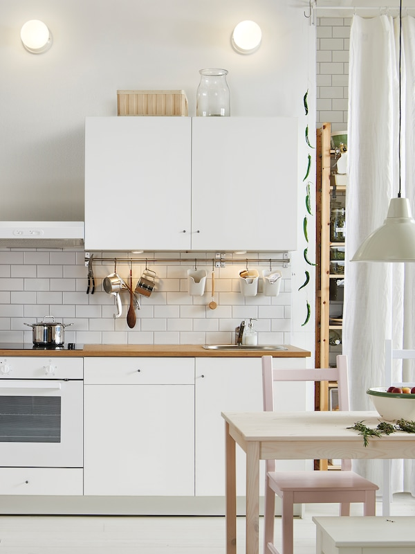 A white KNOXHULT kitchen with a stainless-steel pot sitting on the hob, pots, pans and utensils hanging from a rail.