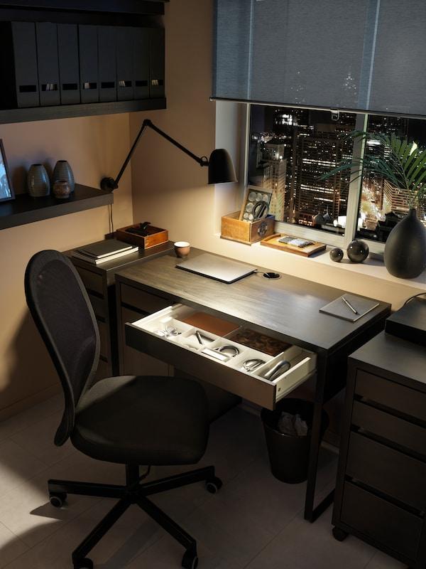 Skrivbord i svart med svart skrivbordsstol.