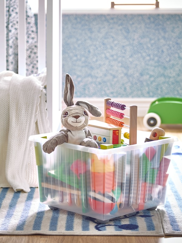 A VESSLA storage crate holding children's toys including a VANDRING HARE soft toy sits on a blue and white GULSPARV rug.
