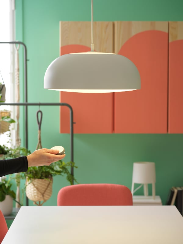 A hanging lamp in white above a white table with a chair, and a hand holding a switch with storage in the background.