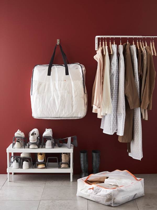 A PÄRKLA storage case hangs from a hook on the wall above a MACKAPÄR shoe rack and next to a MULIG clothes bar.