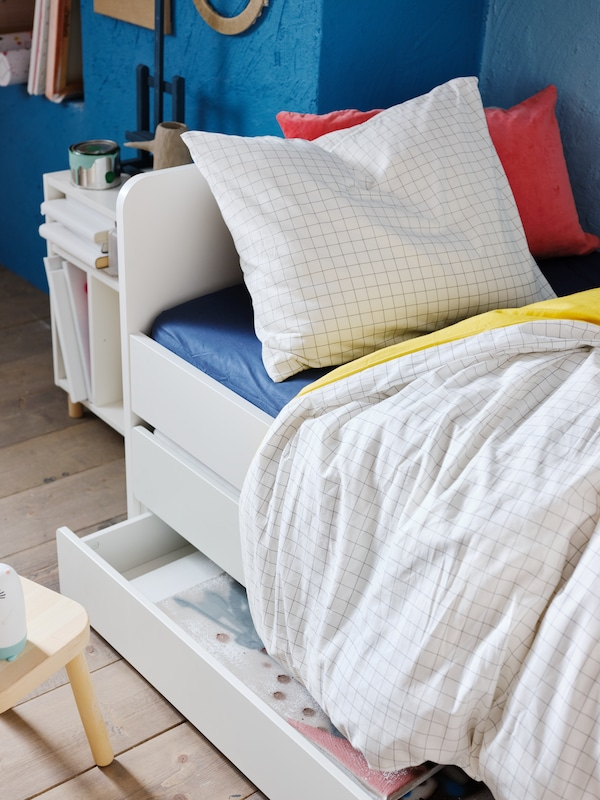 Part of a SLÄKT bed with underbed and storage with a pillow and a duvet in a VÄNKRETS quilt cover and pillowcase.