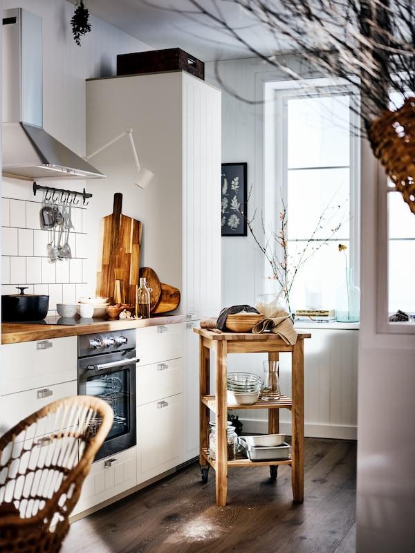 Une cuisine lumineuse avec une table de cuisson à induction MATTMÄSSIG installée sur un plan de travail en bois, à côté d'un marchepied BEKVÄM.