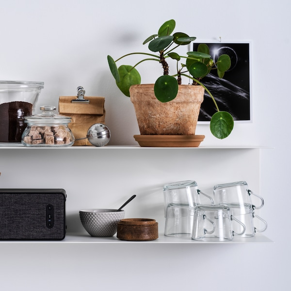 Two white BOTKYRKA shelving units on a white wall with glass coffee cups, a SYMFONISK speaker, and a potted plant.