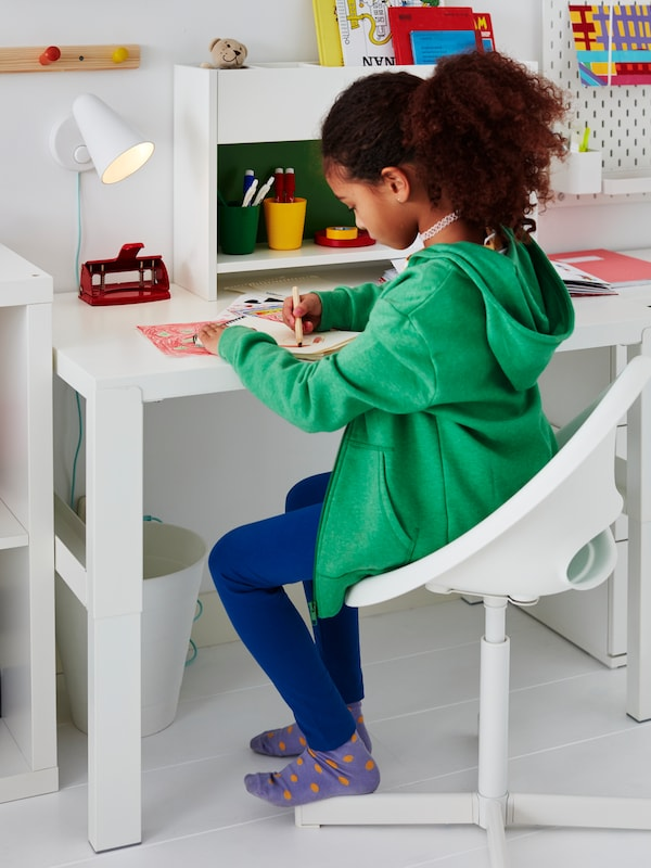 A child sits on a LOBERGET/SIBBEN children's desk chair at a white PÅHL desk with add-on unit. She is drawing a picture.
