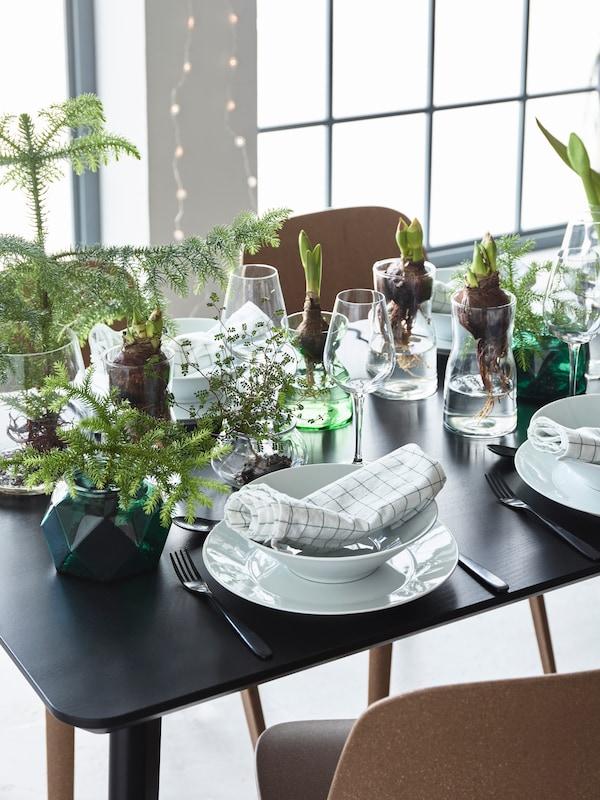 Et dækket bord med masser af vintergrønt, gran og løgplanter.