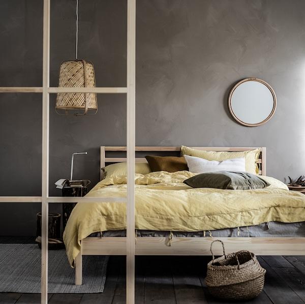 Cama TARVA con ropa de cama PUDERVIVA en amarillo. En la pared hay un espejo HINDÅS y, al otro lado de la cama, una lámpara de techo KNIXHULT.