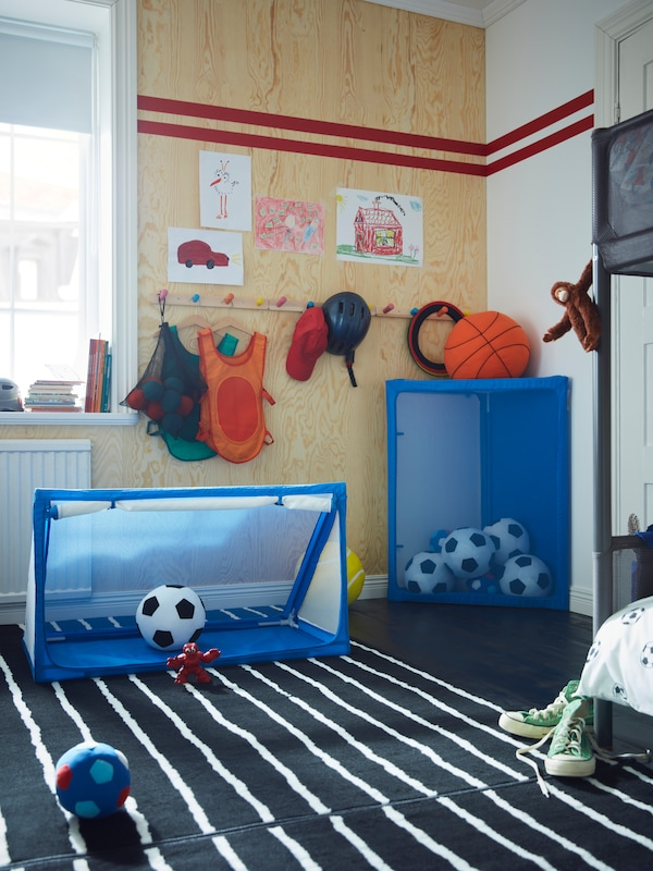 Two SPORTSLIG ball storage/goals in a bedroom. One is being used as a football net, the other is storing more footballs.