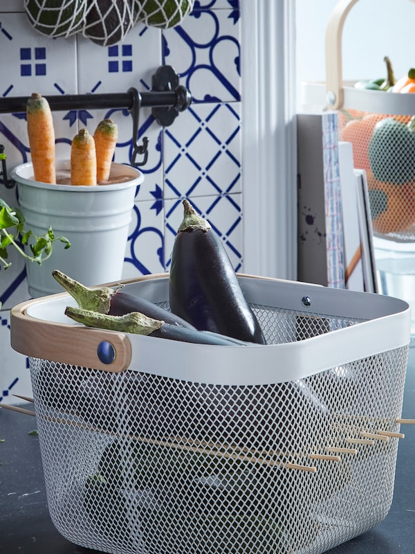 A RISATORP basket, cube-shaped, full of aubergines, and perforated by skewers to create a shelf or partition halfway up.