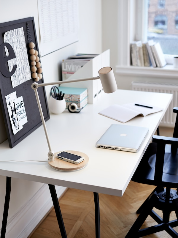A work lamp on a desk with a mobile device, closed laptop, a small noticeboard and other office supplies on the desk.