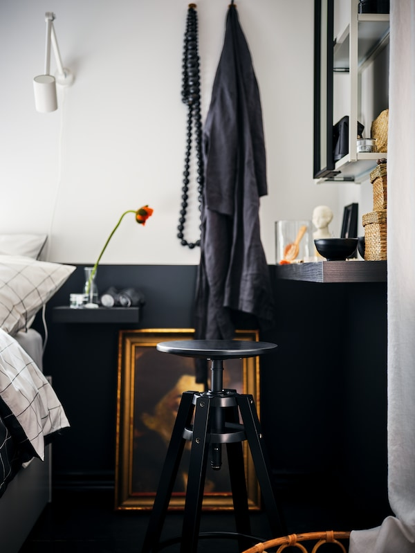 Ein Bettbereich mit einem schwarzbraunen LACK Regal als Ablagetisch, u. a. mit einem schwarzen DALFRED Barhocker und einem ENHET Spiegelschrank.