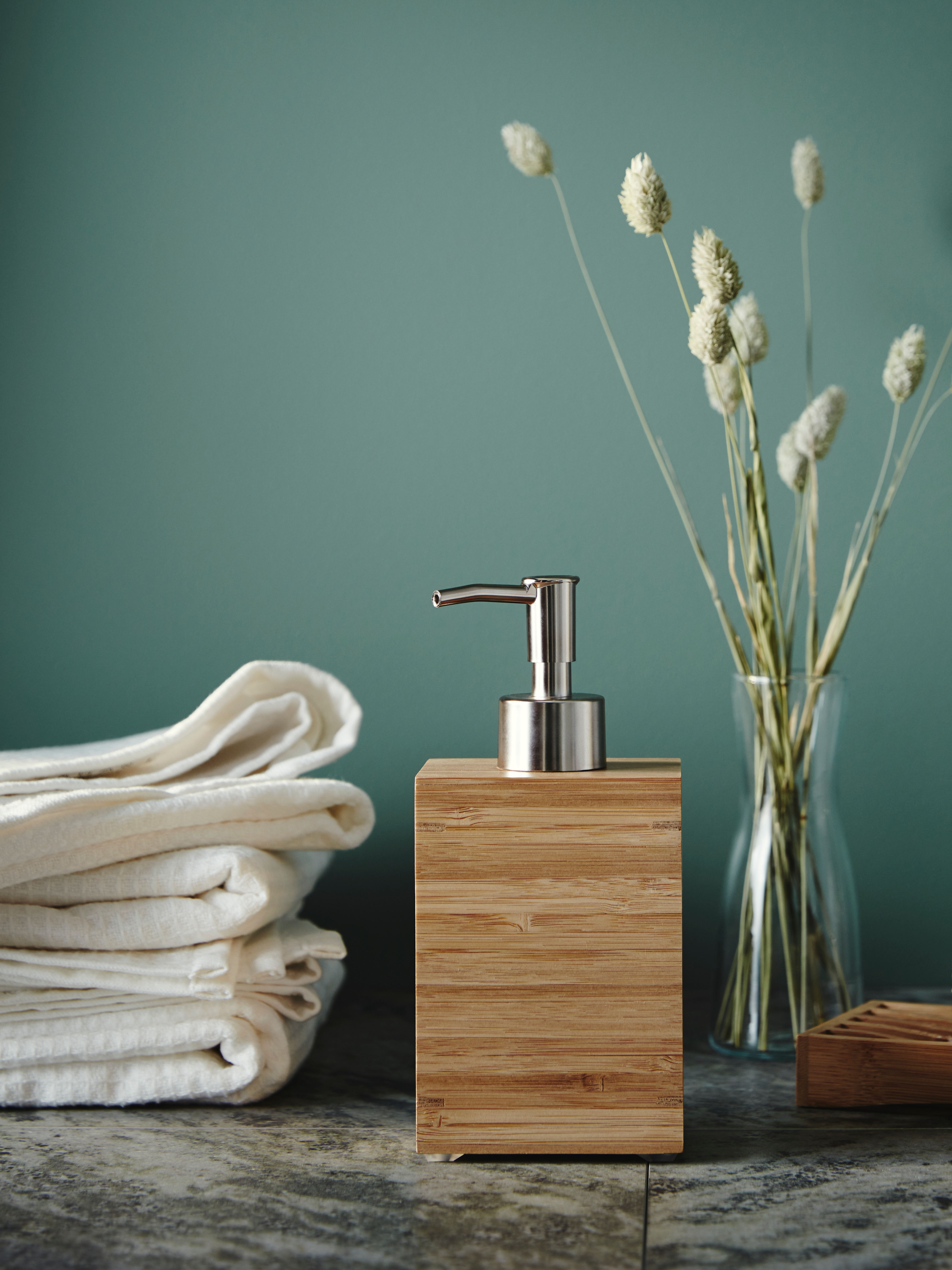 A rectangular, bamboo DRAGAN soap dispenser is next to a matching soap dish and a vase of dried flowers on a tiled surface.