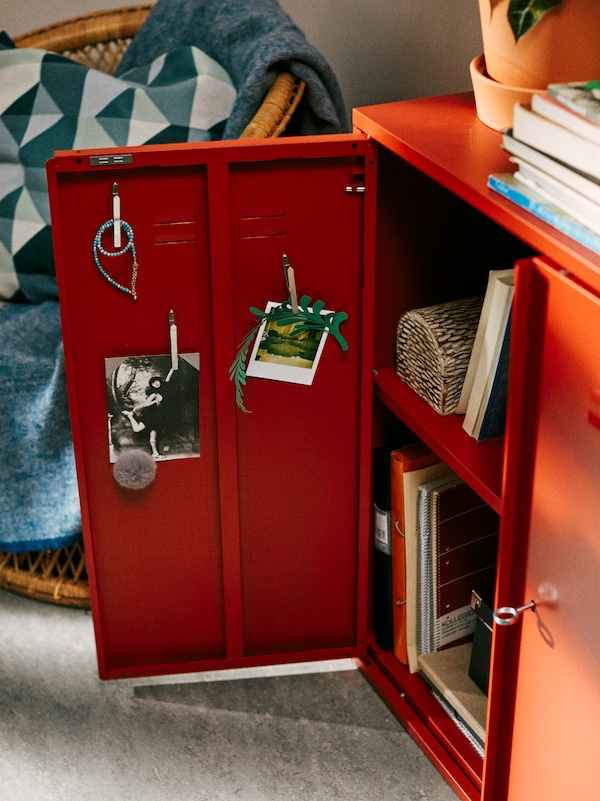 A red IVAR cabinet stands in a student's bedroom, with one door open showing film photos displayed inside the door.
