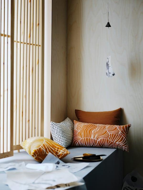 Dos cojines SVAMPMAL en amarillo oscuro y blanco, un cojín FJÄLLTIMOTEJ en blanco y negro y otro cojín junto a la ventana.