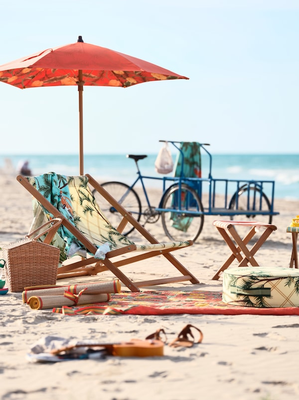 A patterned beach chair with an umbrella and towels, standing on beach sand. A blue bicycle stands in the background.