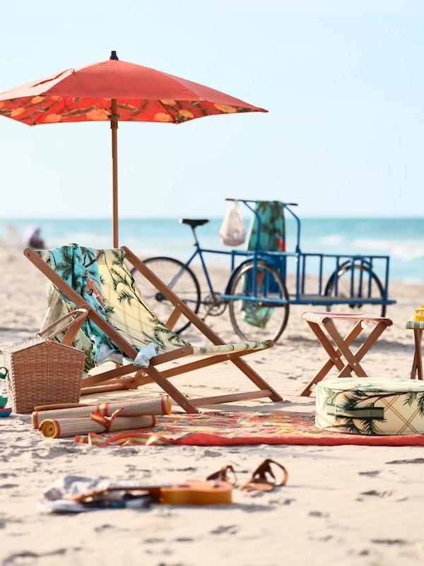 Silla de playa estampada junto a una sombrilla y varias toallas colocadas sobre la arena de la playa. Se ve una bicicleta azul de fondo.