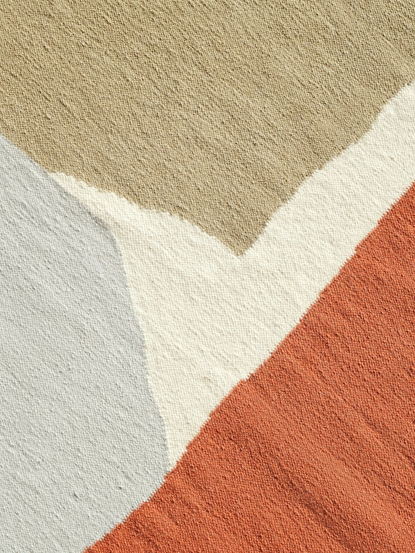 Details of the beige, white, orange and grey patterns of abstract shapes on the TVINGSTRUP handmade rug.