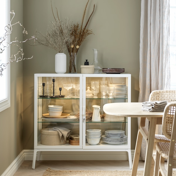 A white glass-door cabinet with integrated lighting stands in the corner of a dining room and is filled with tableware.