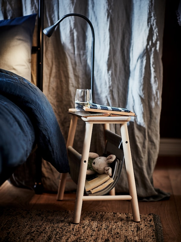 Section of a bed with dark blue linen. On a rug beside it is a stool used as a bedside table, holding books and a glass.