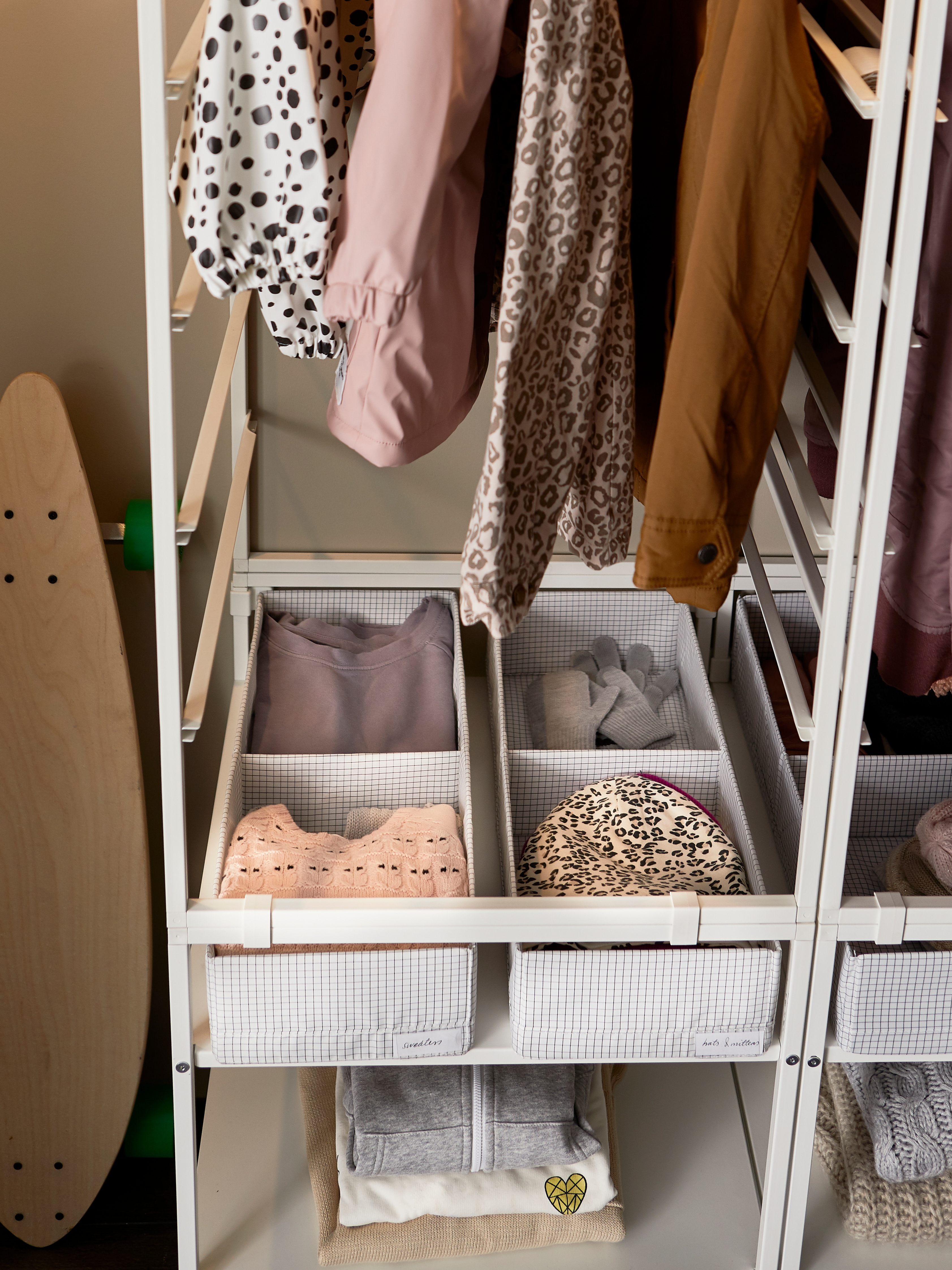 Bottom shelves of a white-coated steel JONAXEL open storage system that have divided boxes holding sweaters, hats and gloves.